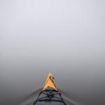 Bootsspitze im Wasser, umgeben von Nebel.