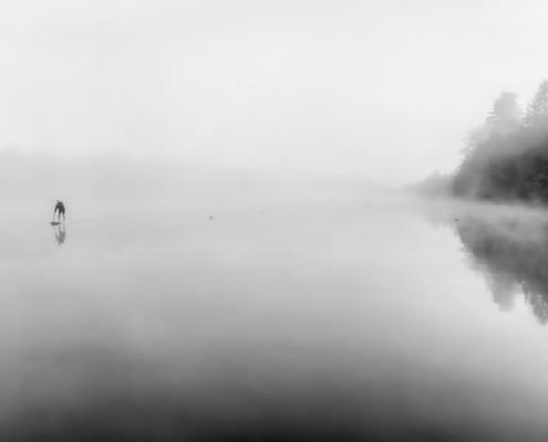 See im Nebel, in der Ferne ein Paddler