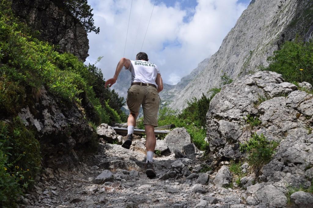 Bergsteiger, der mit Ausdauer schnell einen steinigen Weg hochläuft.