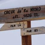 """Holzschilder mit französischer Schrift: """"hier lang"""" oder """"da lang"""" - man kann nur einen Kardinalfehler begehen bei dieser Wegweisung."""