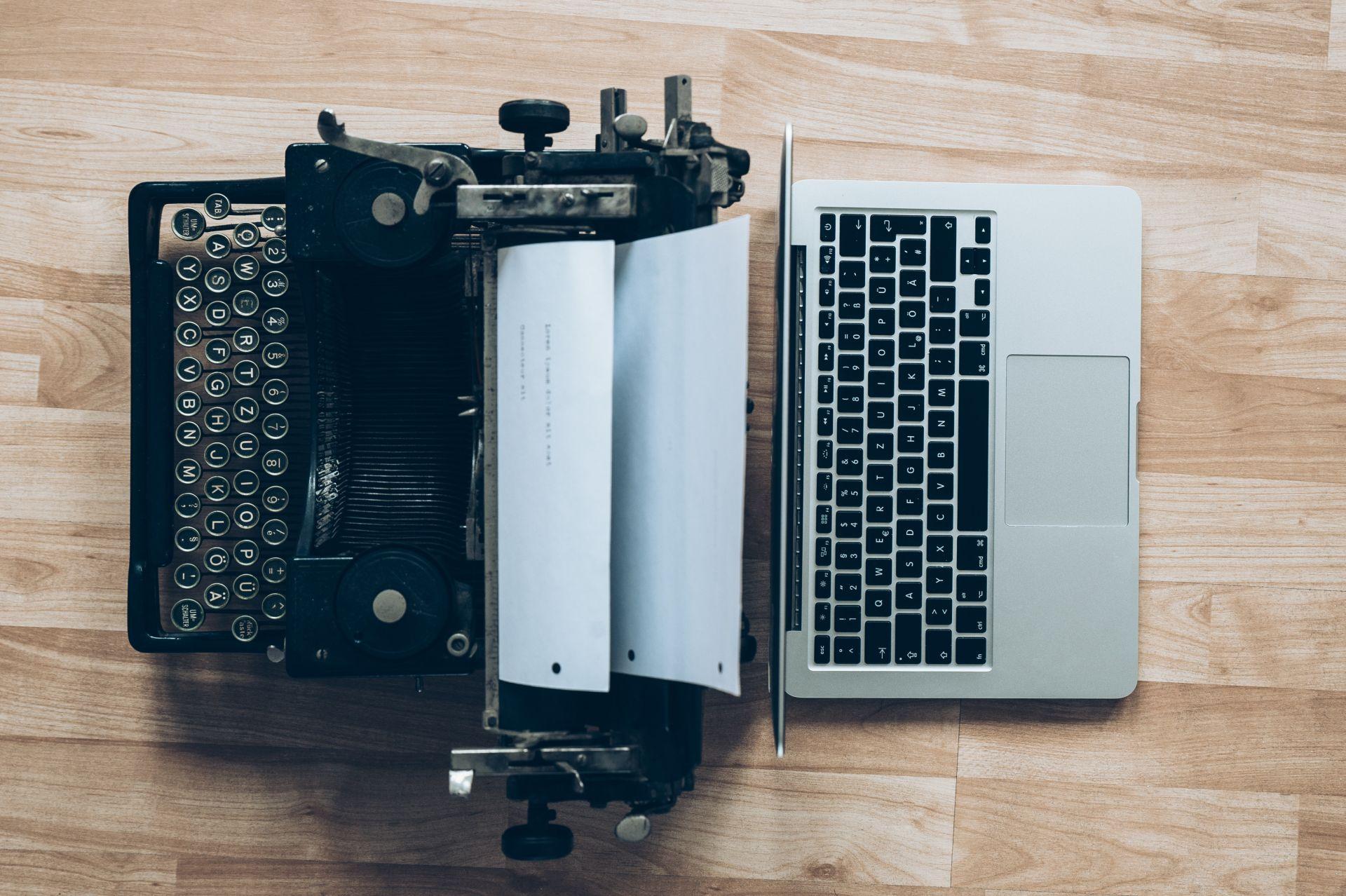 Antike schwarze Schreibmaschine versus Digitalisierung in Form eines  modernen weißen Laptops.